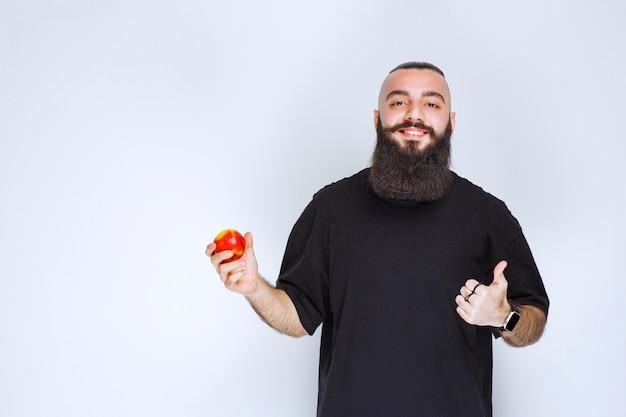 Мужчина с бородой держит красное яблоко или персик и наслаждается вкусом.