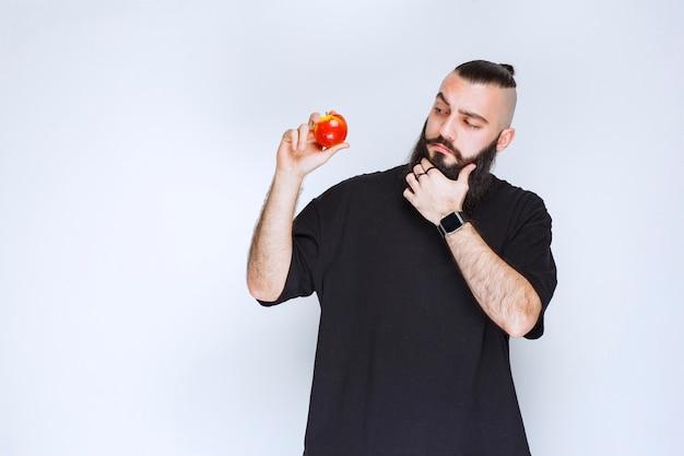 Человек с бородой держит красное яблоко или персик и думает.