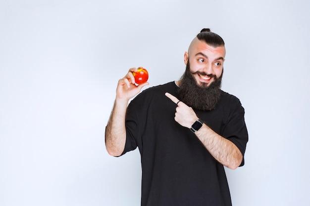 Мужчина с бородой держит красное яблоко или персик. Бесплатные Фотографии
