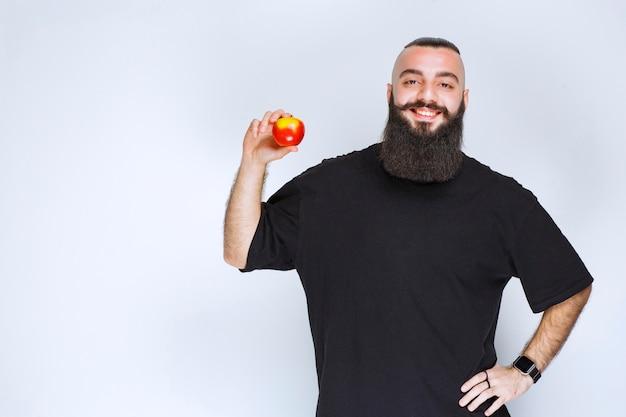 Мужчина с бородой держит красное яблоко или персик.