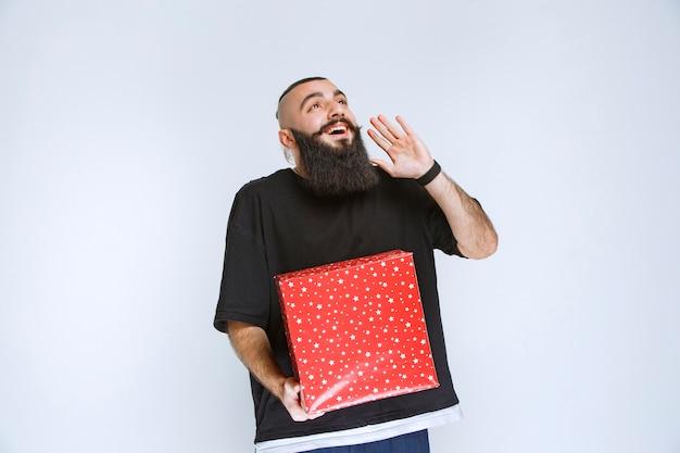 빨간색 선물 상자를 들고 누군가에게 전화를 걸거나 속삭이는 수염을 가진 남자.