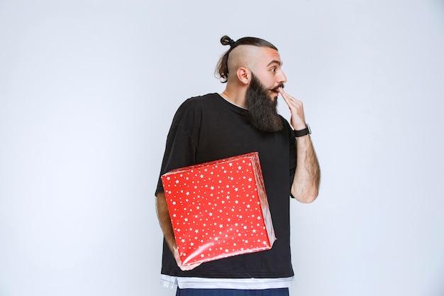 Мужчина с бородой держит красную подарочную коробку и выглядит смущенным и напуганным.