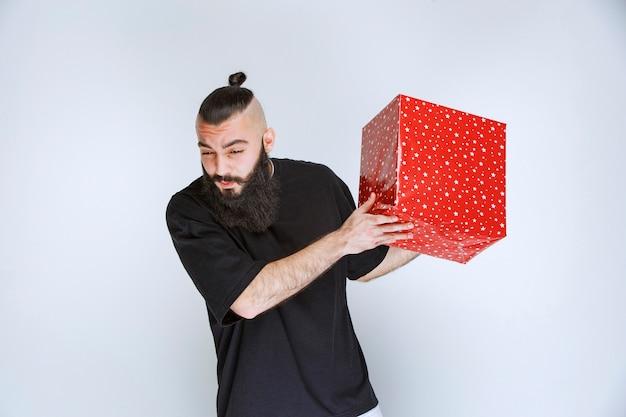 빨간색 선물 상자를 들고 수염을 가진 남자는 혼란스럽고 겁에 질려 보입니다.