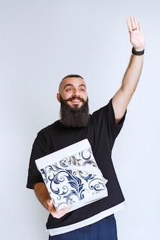 Мужчина с бородой держит бело-синюю подарочную коробку и кому-то звонит.