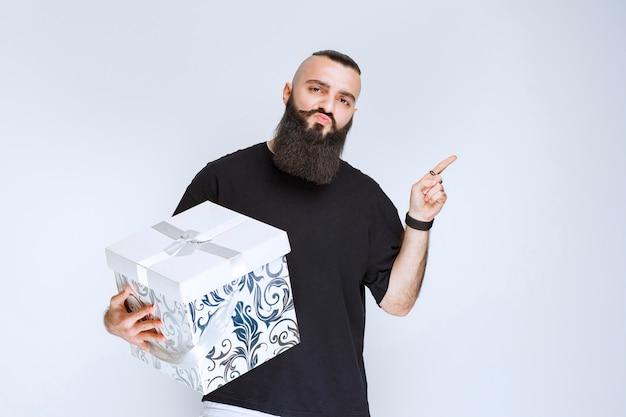 Мужчина с бородой держит бело-синюю подарочную коробку и демонстрирует ее.
