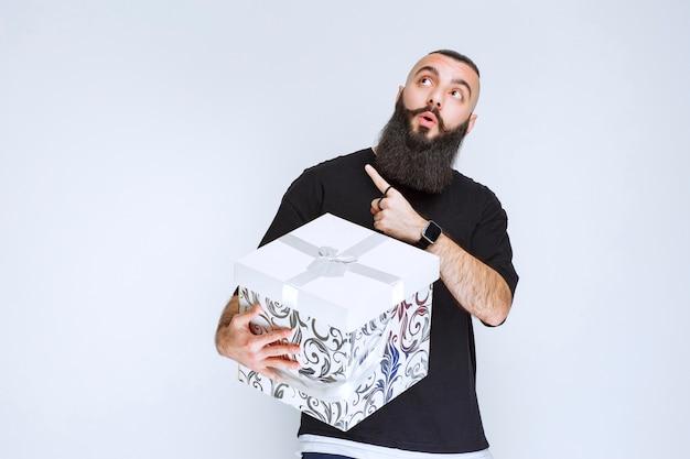 흰색 파란색 선물 상자를 들고 그것을 보여주는 수염을 가진 남자.