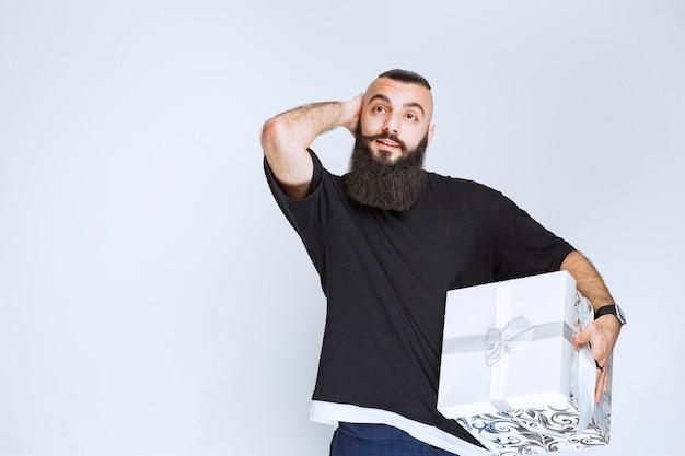 白青のギフトボックスを保持し、それを示すひげを持つ男。