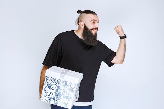 白青のギフトボックスを保持し、成功を感じているひげを持つ男。