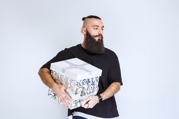 白青のギフトボックスを持って、がっかりしているように見えるひげを持つ男。