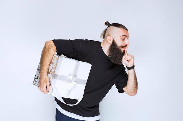 Мужчина с бородой держит бело-синюю подарочную коробку, указывая в рот и прося тишины.