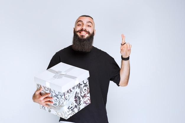 Человек с бородой держит белую синюю подарочную коробку, улыбаясь и чувствуя себя счастливым.