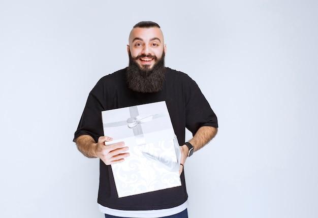 웃 고 행복 한 느낌이 흰색 파란색 선물 상자를 들고 수염을 가진 남자.