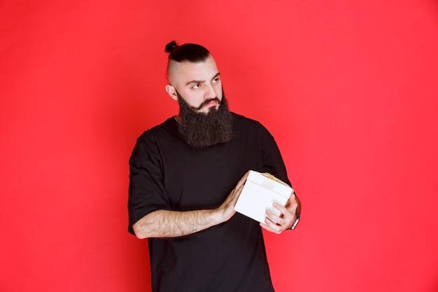 Мужчина с бородой держит белую подарочную коробку и сомневается в том, что внутри.