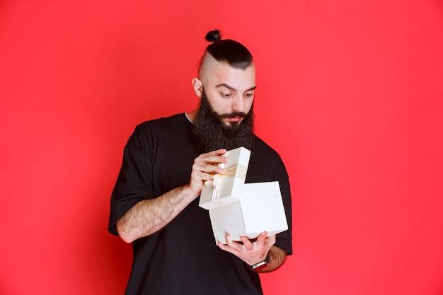 흰색 선물 상자를 들고 수염을 가진 남자와 안에 무엇이 있는지 의심스러워 보입니다.