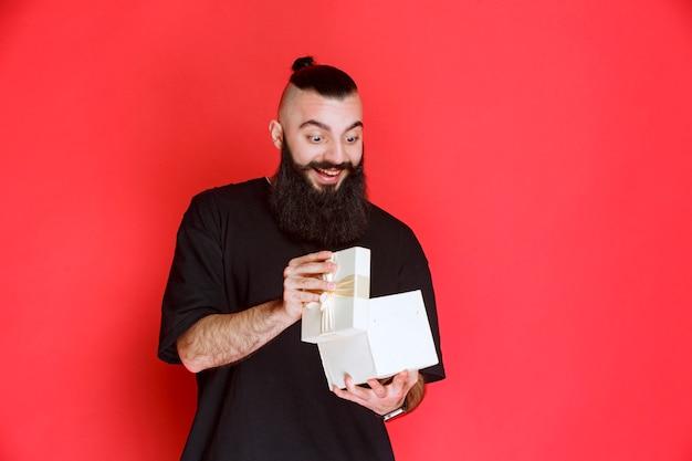 Мужчина с бородой держит белую подарочную коробку и открывает ее от волнения.