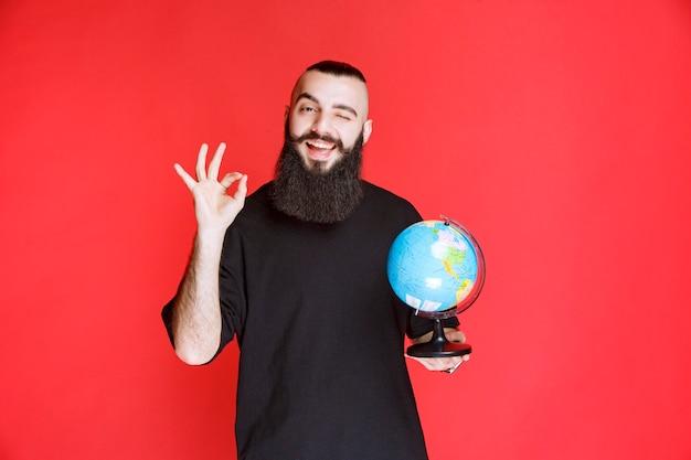 Человек с бородой держит глобус и наслаждается им.