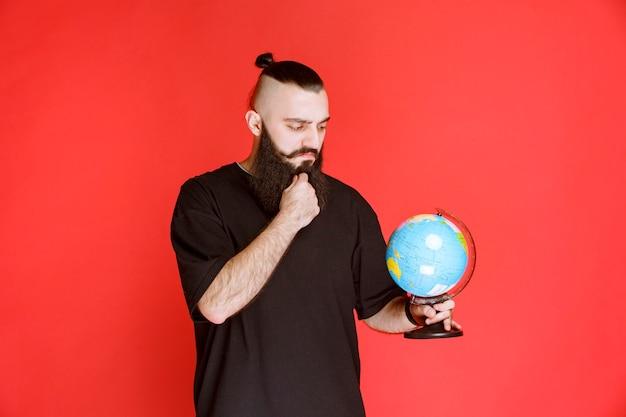 ひげを生やした男が世界の地球儀を持って、その上の場所を探しています。
