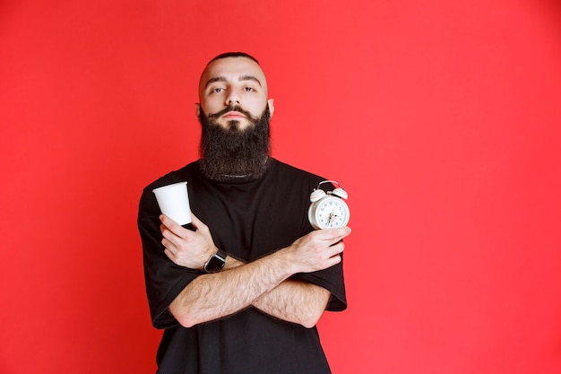 Man with beard holding an alarm clock and a cup of coffee.