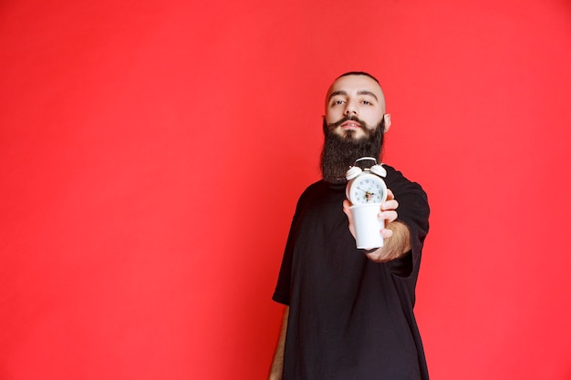Man with beard holding an alarm clock and having a cup of coffee.