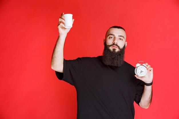 Мужчина с бородой держит будильник и чашку кофе.