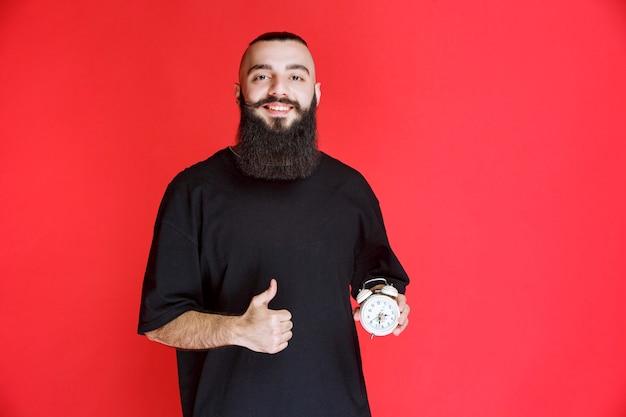 目覚まし時計を持って製品を楽しんでいるひげを持つ男。