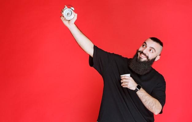 Мужчина с бородой держит будильник и выпивает чашку кофе.