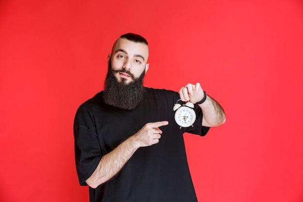 제품으로 알람 시계를 들고 홍보하는 수염을 가진 남자.