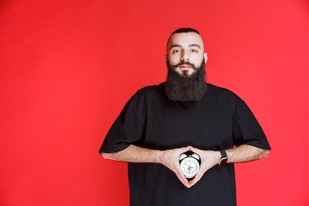 目覚まし時計を商品として持って宣伝しているあごひげを持つ男。 無料写真