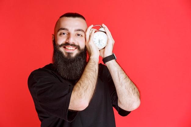 Мужчина с бородой держит и продвигает будильник как продукт.
