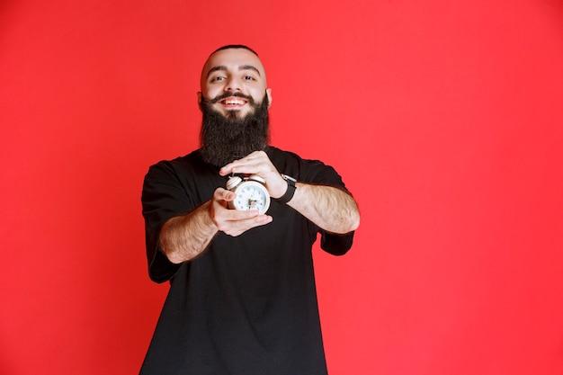 目覚まし時計を商品として持って宣伝しているあごひげを持つ男。