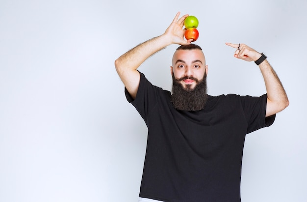 Man with beard holding apples over his head.