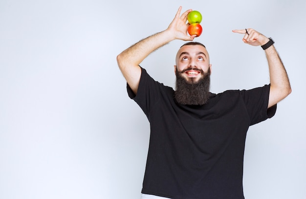 Uomo con la barba che tiene le mele sopra la sua testa.