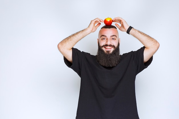 Мужчина с бородой держит яблоки над головой.