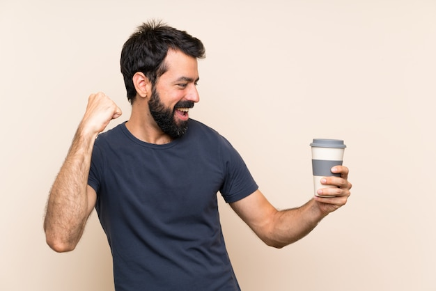 Man with beard holding a coffee celebrating a victory