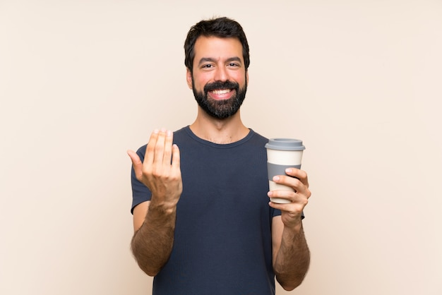 Man with beard holding a coffee inviting to come with hand. happy that you came