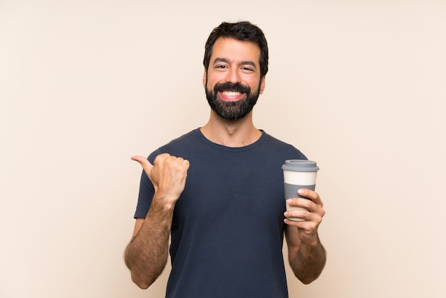Man with beard holding a coffee pointing to the side to present a product