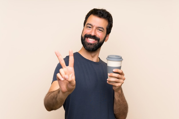 Man with beard holding a coffee smiling and showing victory sign