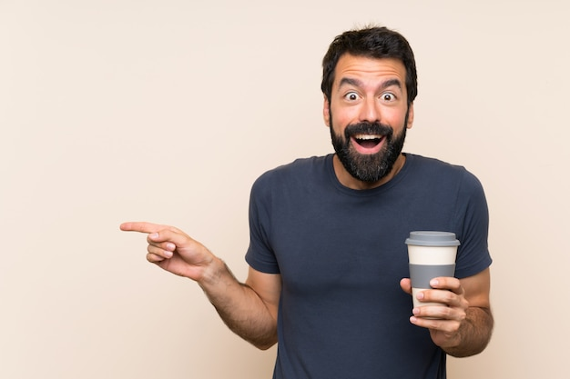 Man with beard holding a coffee surprised and pointing finger to the side