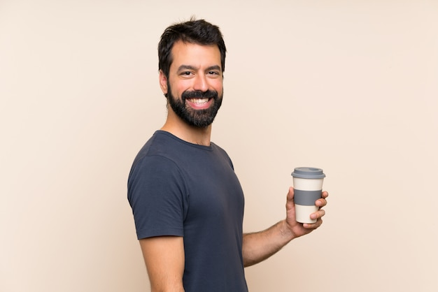 Man with beard holding a coffee with surprise facial expression