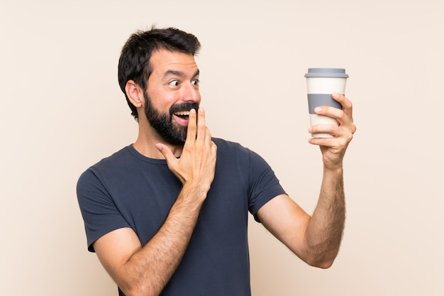Man with beard holding a coffee with surprise and shocked facial expression