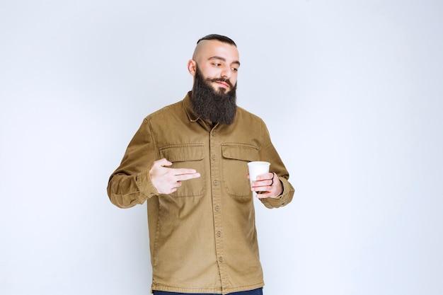 Uomo con la barba che tiene una tazza di caffè in una tazza usa e getta.