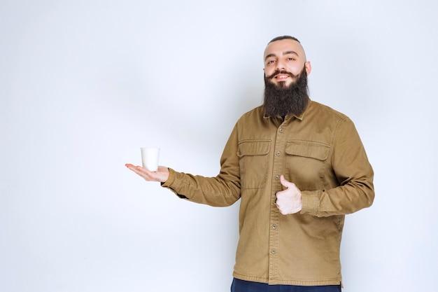 Uomo con la barba che tiene una tazza di caffè e si gode il gusto.