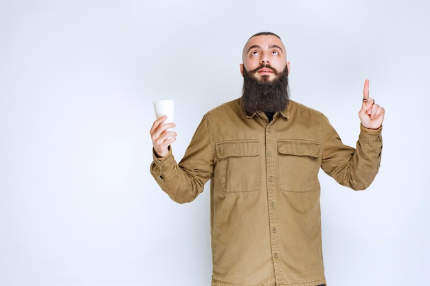 Man with beard holding a cup of coffee and thinking.