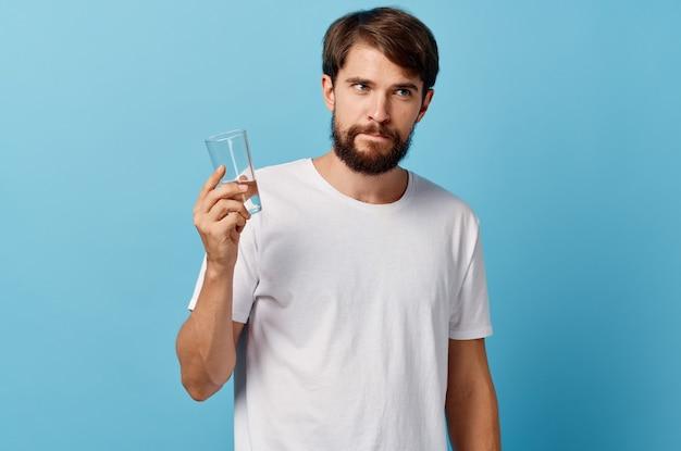 Человек с бородой, держащий стакан воды в руке на синем фоне, белая футболка модели обрезанный вид