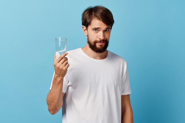 Человек с бородой, держа в руке стакан воды
