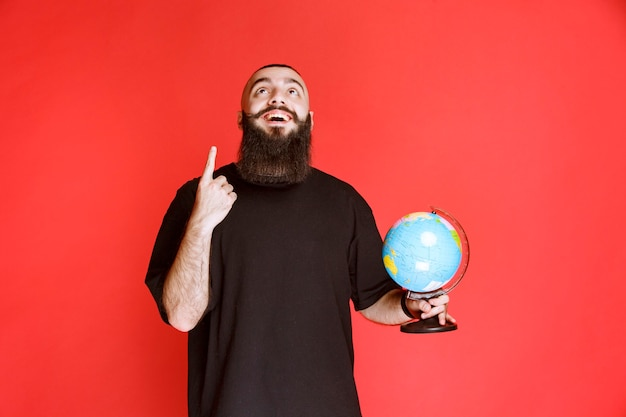 Man with beard holding a globe and pointing to somewhere.