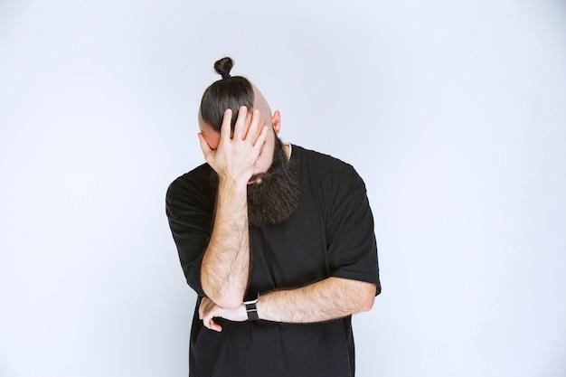 頭が痛くて頭を抱えているひげを生やした男性。