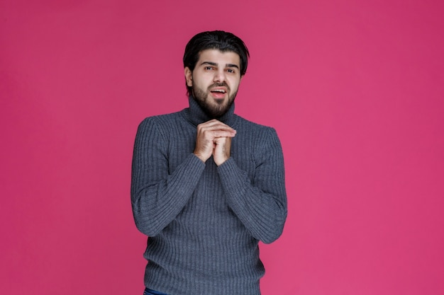 Man with beard holding his hands in a manner like he is praying or wishing something.