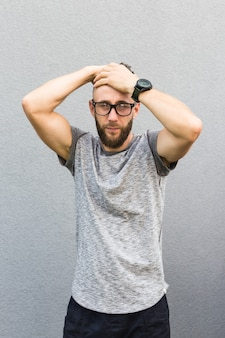 Man with beard holding his head. isolated on grey wall.