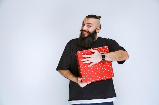 彼の赤いギフトボックスを保持し、それを楽しんで、幸せを感じているひげを持つ男。